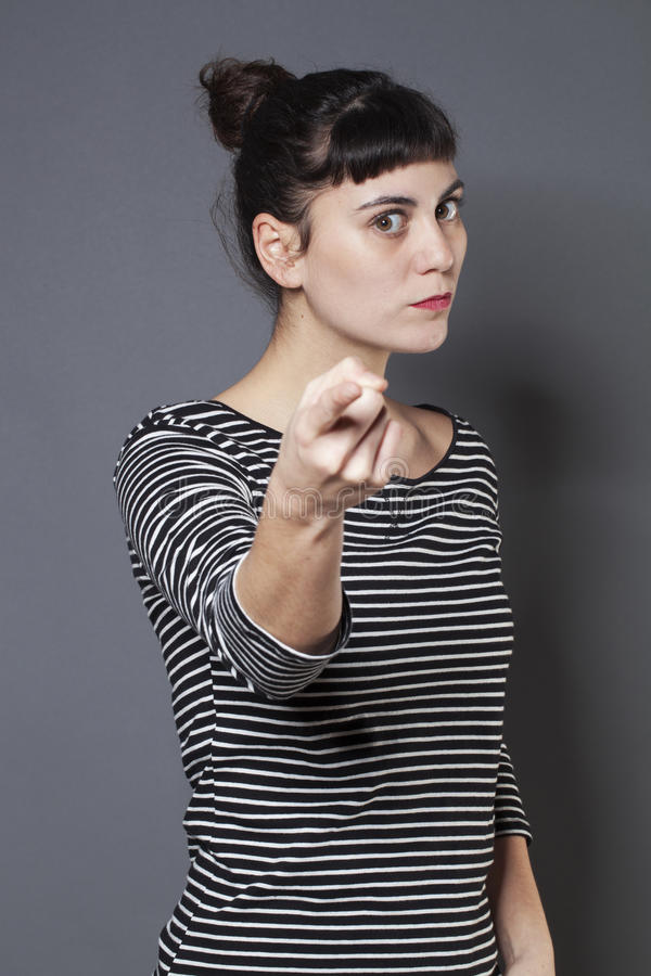Bossy 20s woman threatening someone with self-assertion. Blaming young brunette woman staring at someone with index finger forward accusing and condemning stock photos
