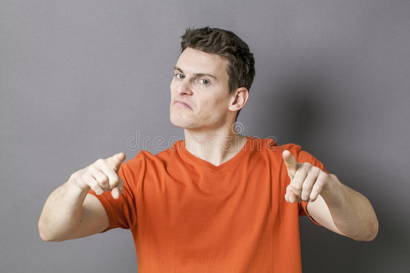 Bossy sporty man accusing someone with hands for blame. Guilt concept - bossy young sporty man accusing or threatening someone with his hands for blame, grey stock photo