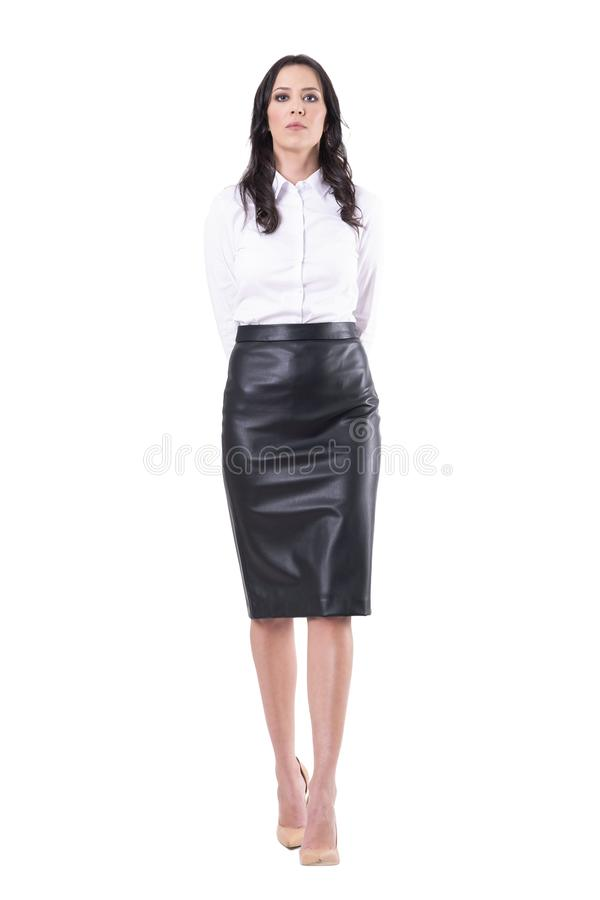 Bossy strict authoritative business woman or teacher walking with hands on back. Full body isolated on white background stock photography