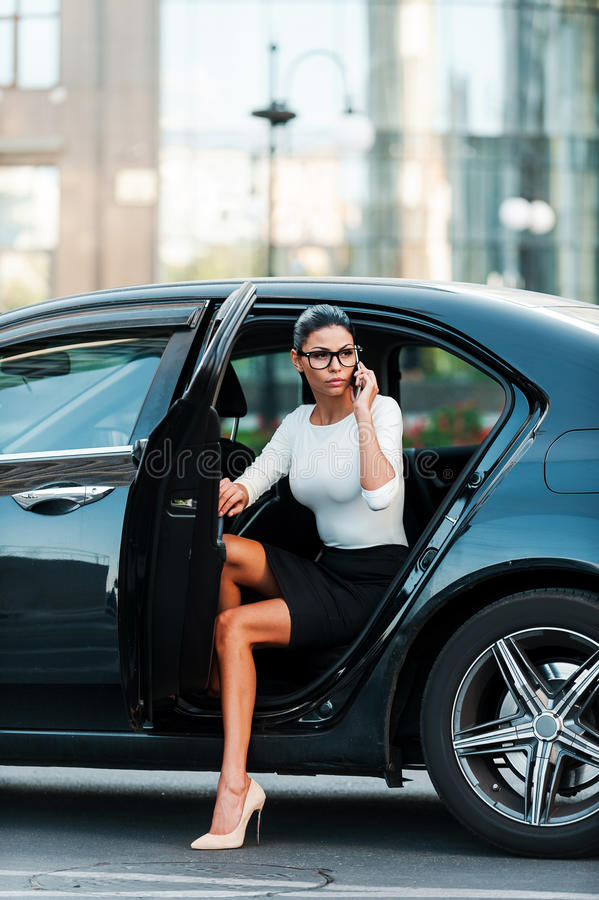 Bossy woman. Confident young businesswoman talking on the mobile phone while coming out her car stock image