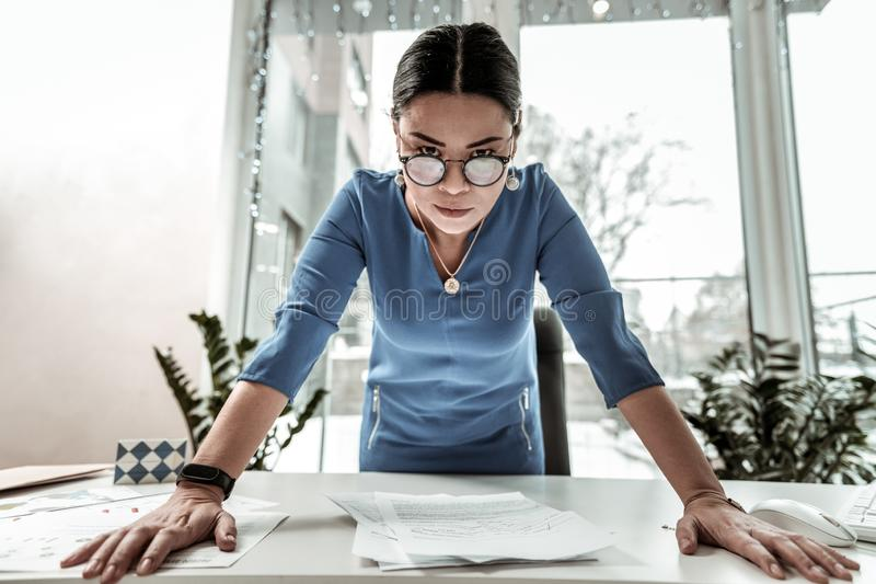 Dark-haired beautiful asian woman in a blue shirt looking bossy royalty free stock photos