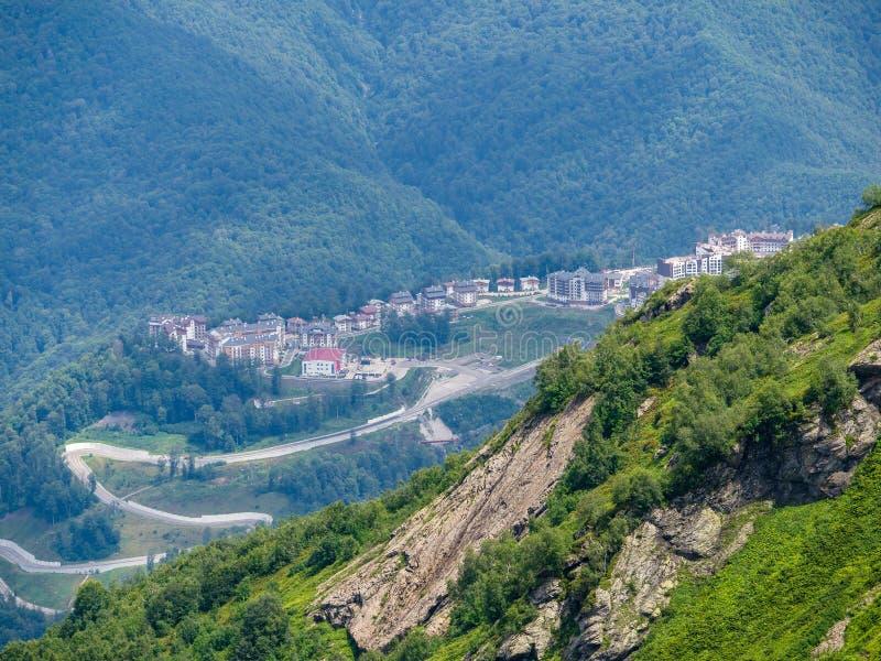 Bostads- hem i den gröna dalen som omges av höga berg Rosa Khutor skidar semesterorten, Krasnaya Polyana, Sochi, Ryssland royaltyfria foton