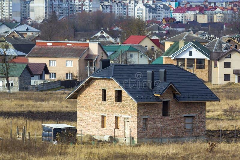 Bostads- hus för splitterny rymlig berättelse för tegelsten två med att belägga med tegel tak- och fönsteröppningar i förorts- gr fotografering för bildbyråer