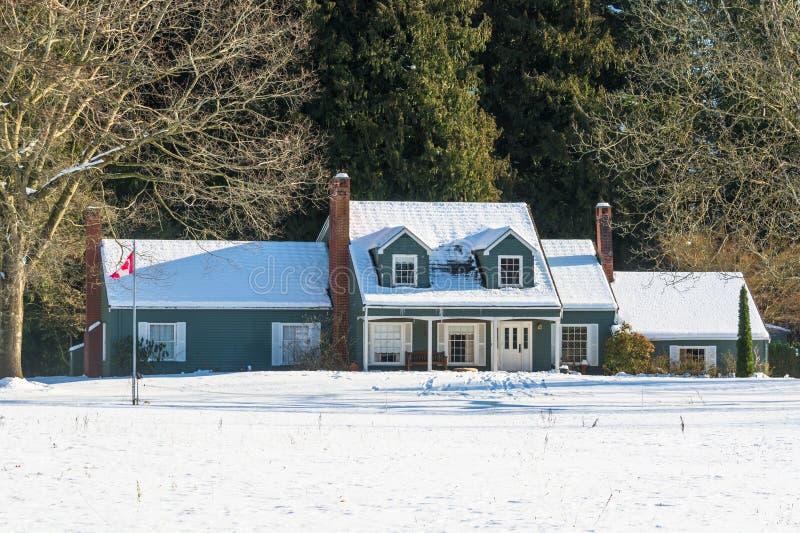 Bostads- hus i snö på en solig dag arkivbild