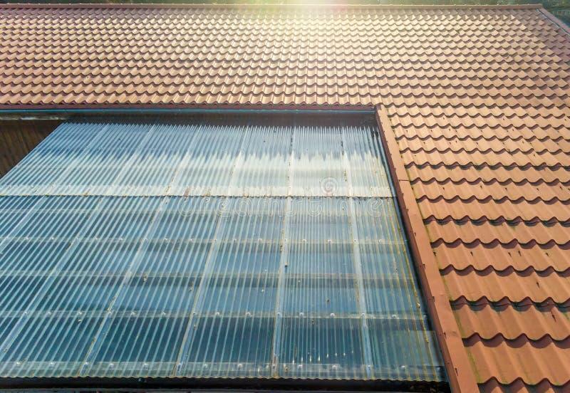 Bostads- hus med tenntaket och genomskinliga korrugerade ark som att taklägga för terrass royaltyfri foto