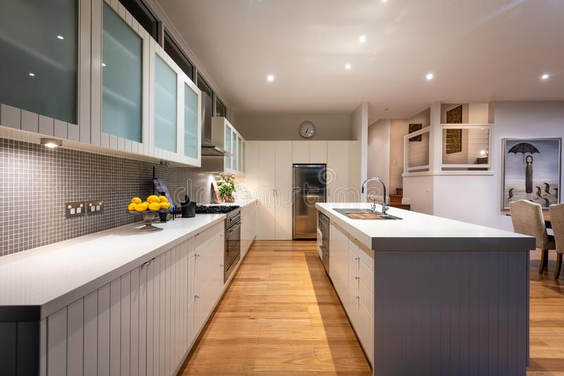 Bostads- kök för lyxigt inhemskt hem med granitbänkblast, kabinetter, belagd med tegel färgstänkbaksida, vasken, ugnen och område arkivbilder