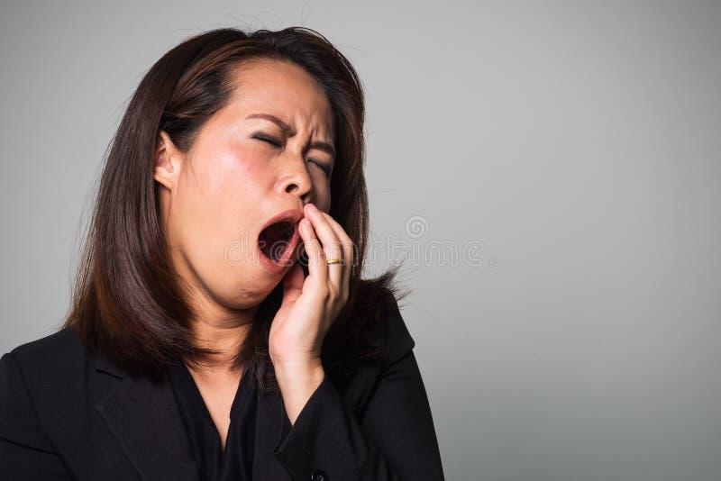 Bostezo asiático de la mujer adulta Emoción cansada y soñolienta Las mujeres de negocios… y su finger está para arriba imagen de archivo