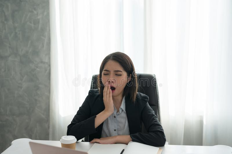 Bostezo soñoliento de la muchacha joven asiática del negocio con el trabajo en la oficina imagenes de archivo