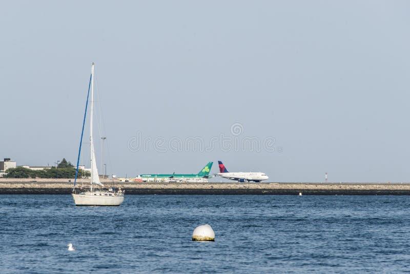 BOSTON EUA 06 09 Vista 2017 do barco de navigação na frente de e dos aviões do delta do aeroporto internacional de Logan prontos  foto de stock