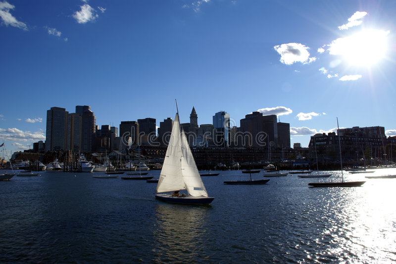 Boston Harbor Downtown Skyline and Sailboat. Sailboat sailing in Massachusetts Boston harbor with downtown skyline cityscape in late afternoon with bright sun in stock photography