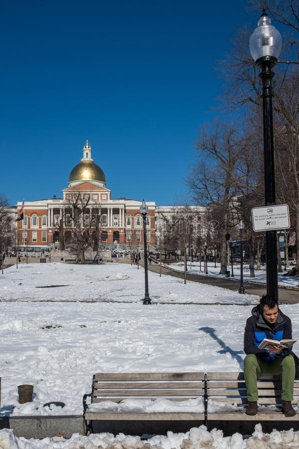 Boston, mA, los E.E.U.U., febrero, 8, 2016: Un hombre joven se encarama en la parte de atrás de banco al aire libre que lee un li foto de archivo libre de regalías