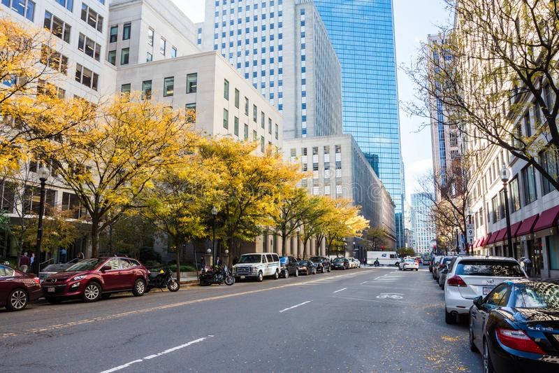 BOSTON - OCTOBER 2017: Fall and yellow trees along the street with cars and business buildings. Boston, USA. Fall and yellow trees in Boston royalty free stock photography