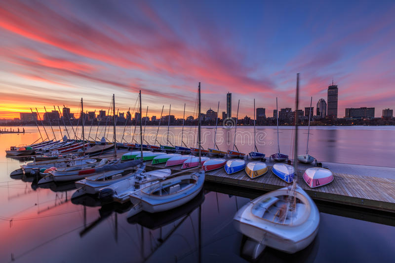 Boston skyline at dawn. Sunrise on the Boston skyline as seen across the Charles River. Moored colorful sailboats in the foreground royalty free stock images