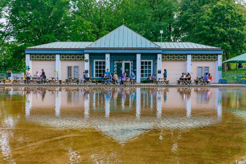 Locals resting at tables by Frog Pond and Frog Pond Pavilion, with their reflections in the water, in Boston Common royalty free stock photography
