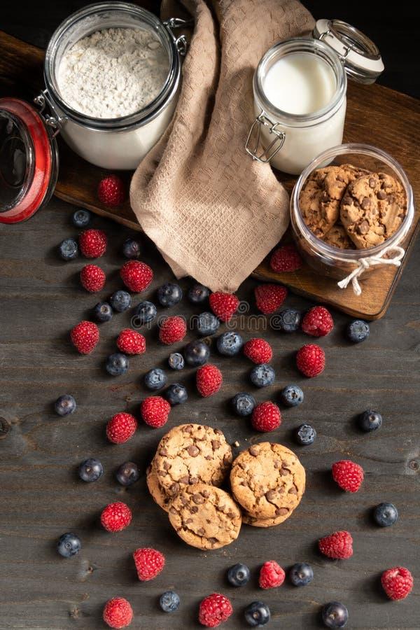 Bosvruchten, eigengemaakte koekjes, melk en bloemlijstbovenkant royalty-vrije stock fotografie