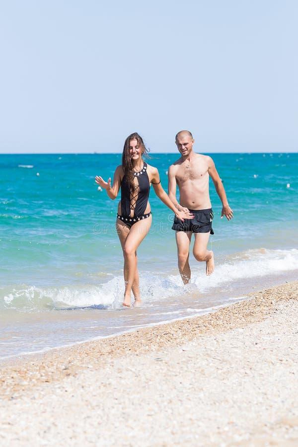 Bosy młodej kobiety i mężczyzna swimwear bieg wzdłuż seashore fotografia royalty free