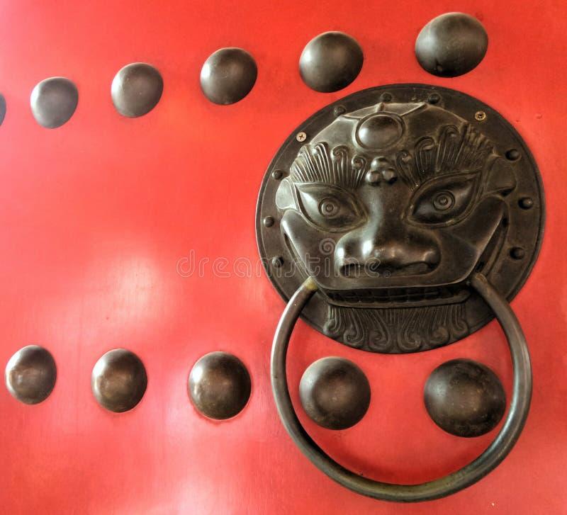 Botão chinês do leão do bronz em portas vermelhas da porta fotos de stock