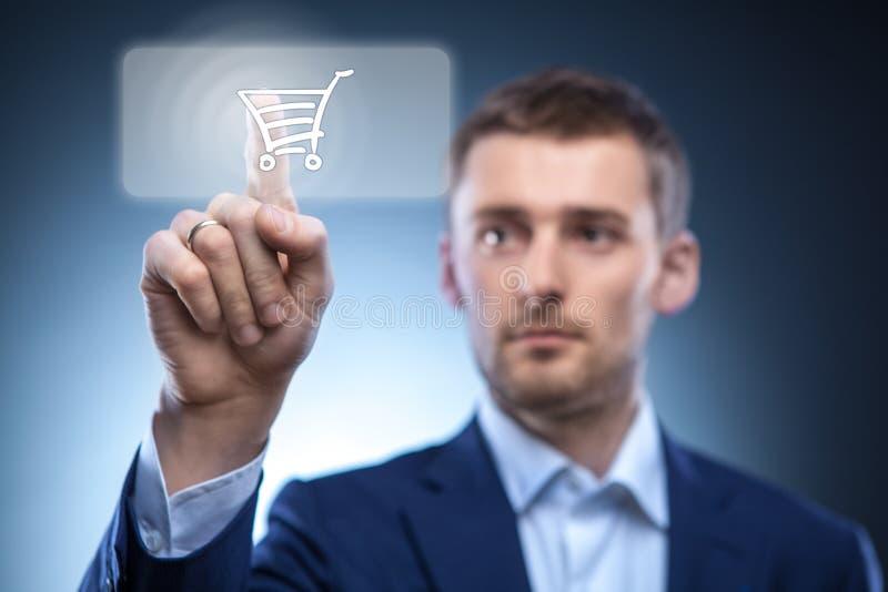 Botão da imprensa do homem de negócios com carrinho de compras imagens de stock royalty free