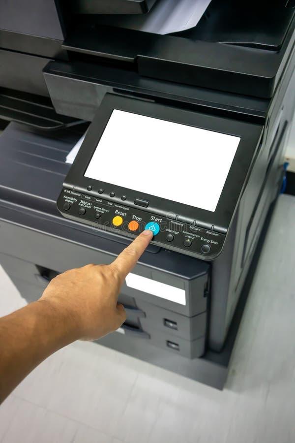 Botão da imprensa da mão do homem do close-up no painel da impressora, máquina da cópia de escritório do laser do varredor de imp fotografia de stock