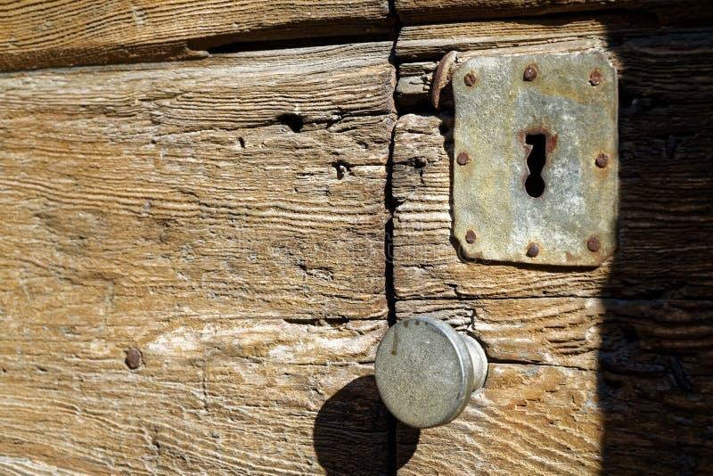 Botão de porta e buraco da fechadura rústicos na porta de madeira velha, estilo do vintage foto de stock royalty free