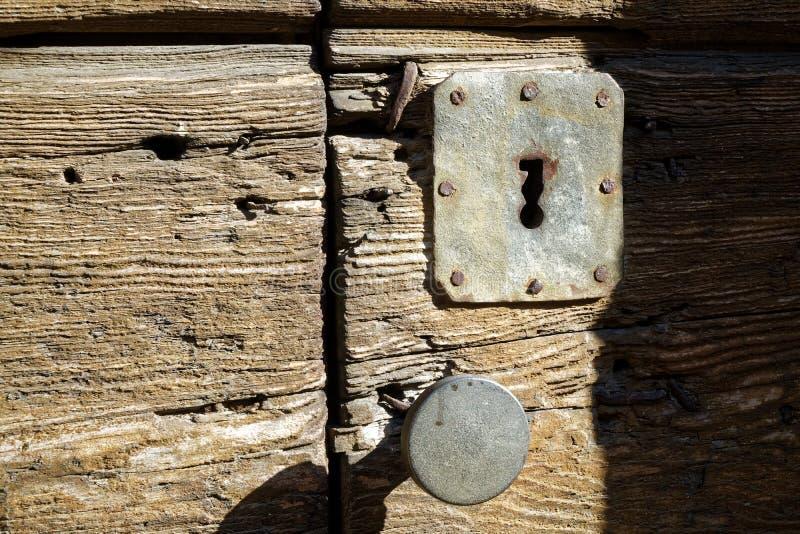 Botão de porta e buraco da fechadura rústicos na porta de madeira velha, estilo do vintage fotos de stock royalty free