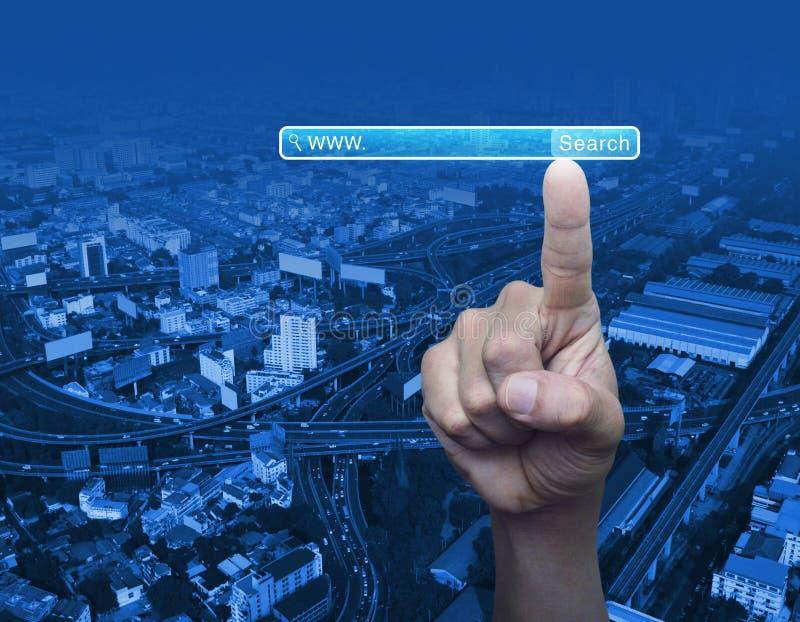 Botão de WWW da busca da pressão de mão sobre o fundo da torre da cidade, gatilho fotos de stock