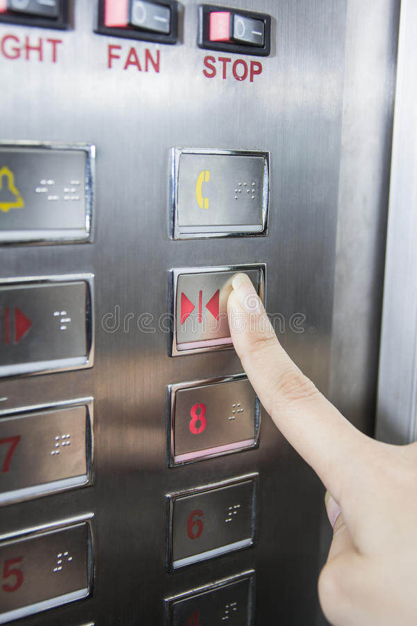 Botão do estar aberto da imprensa da mão no elevador imagens de stock