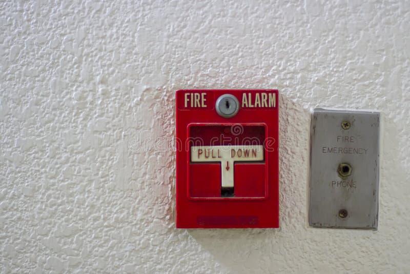 Botón antiguo rojo la alarma de incendio con la pared blanca imagen de archivo