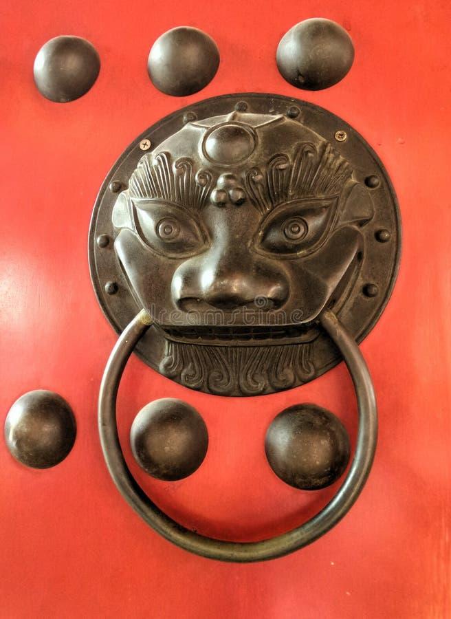 Botón chino del león del bronz en puertas rojas de la puerta imagen de archivo