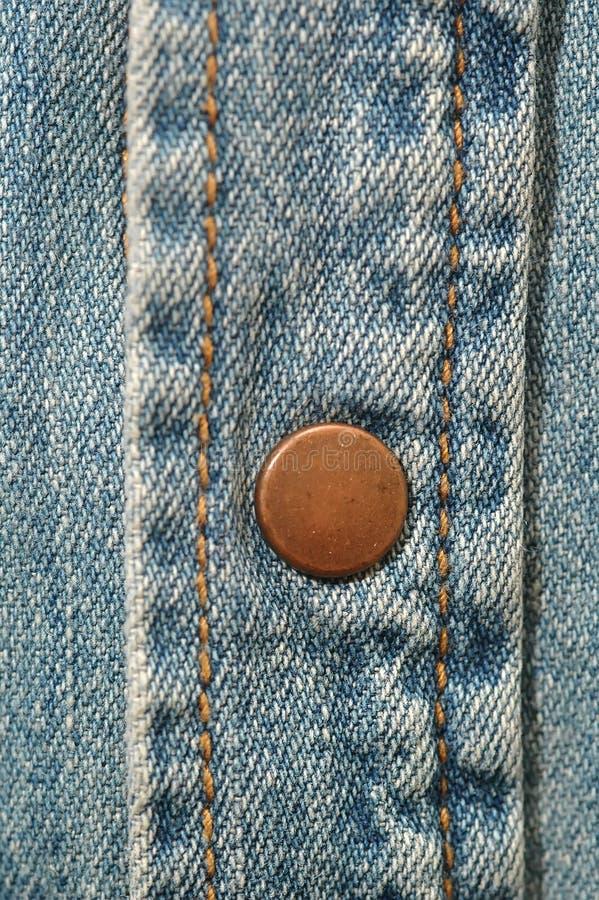 Botón de cobre amarillo en el dril de algodón imagen de archivo