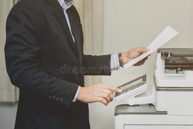 Botón de la mano del hombre de negocios en el panel de la impresora de la copia fotografía de archivo libre de regalías
