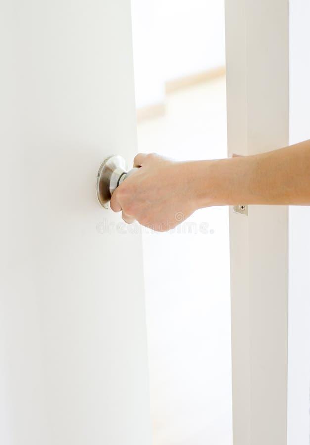 Botón de puerta de abertura de la mano, puerta blanca foto de archivo