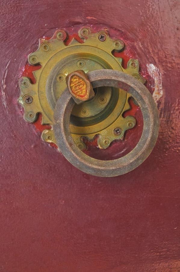 Botón de puerta de cobre amarillo de oro del vintage chino en puerta roja imágenes de archivo libres de regalías