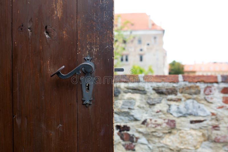 Botón de puerta rasguñado vintage de una puerta de madera marrón contra un panorama de la ciudad imagen de archivo libre de regalías