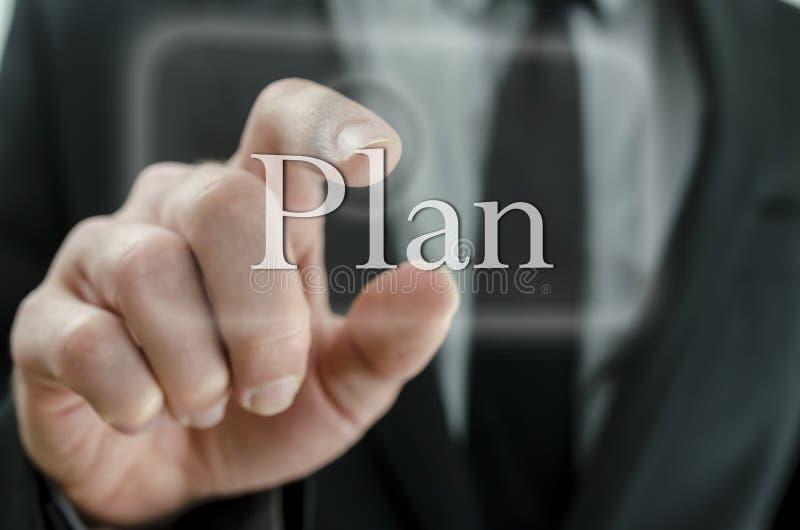 Botón del plan del presionado a mano del hombre de negocios en un interfa de la pantalla táctil imagen de archivo