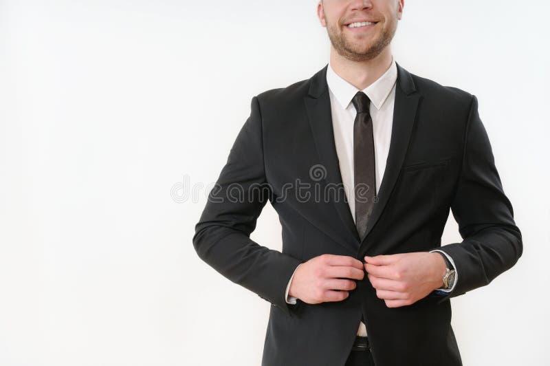 Botón sonriente el lateral de carrocería del hombre de negocios encima de su traje negro en blanco imagenes de archivo