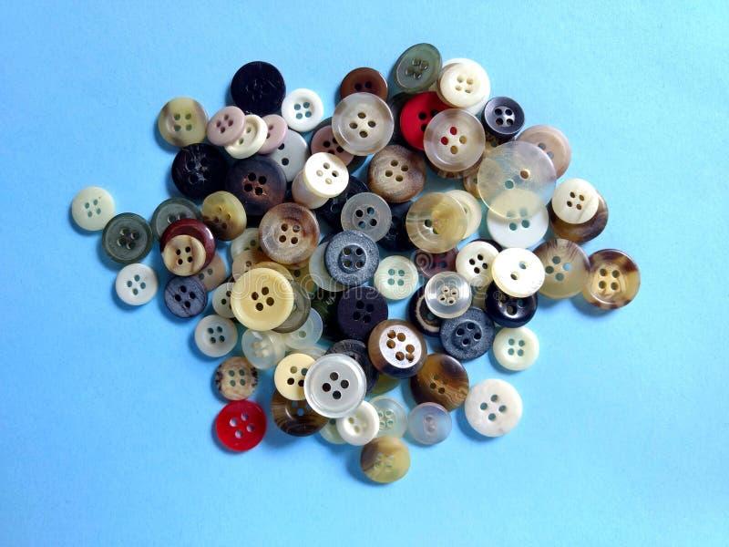 Botões coloridos da roupa no fundo azul foto de stock royalty free