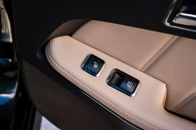 Bot?es do controle e para comutar o assento caloroso e a abertura da janela na porta de carro com estofamento de couro para contr fotografia de stock royalty free