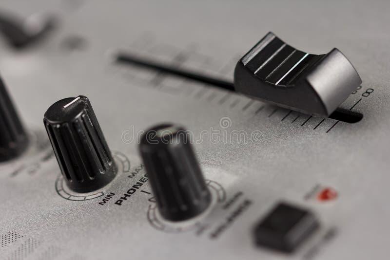 Botões e fader de um misturador do DJ fotos de stock