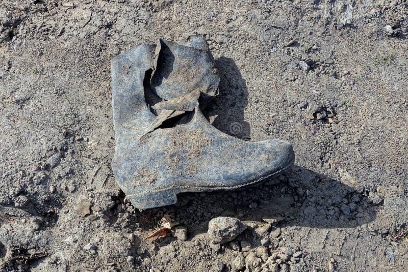 Bota de borracha áspera suja na terra imagem de stock