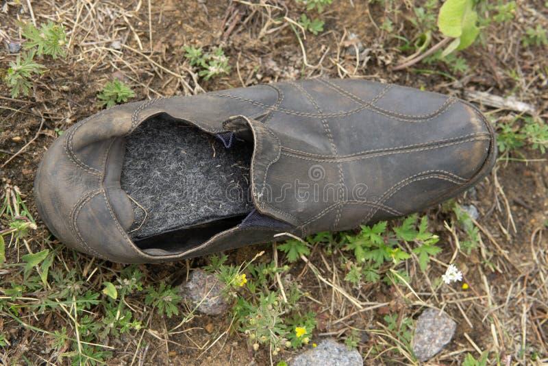 Bota de couro abandonada velha que encontra-se na grama imagens de stock