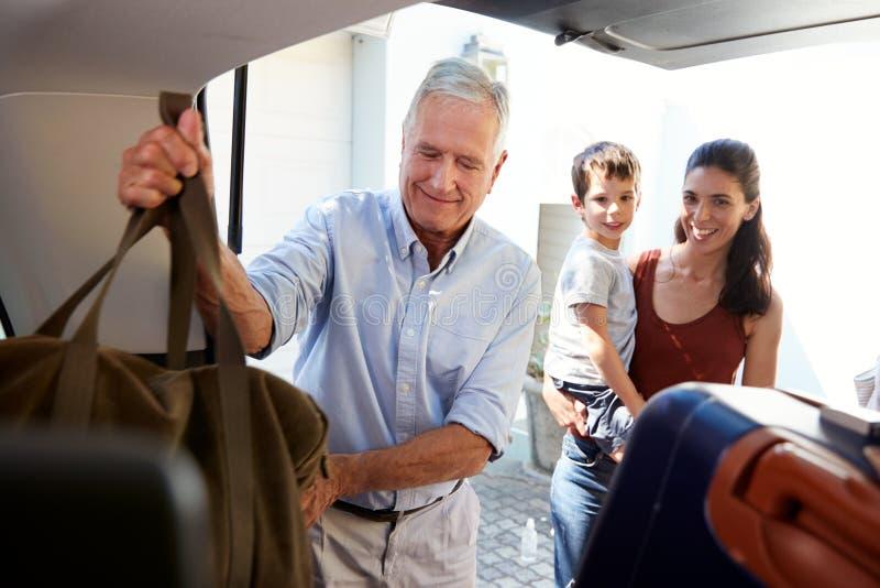 Bota de embalagem superior do carro do homem branco com a bagagem do feriado, olhada por seus filha e neto adultos fotos de stock