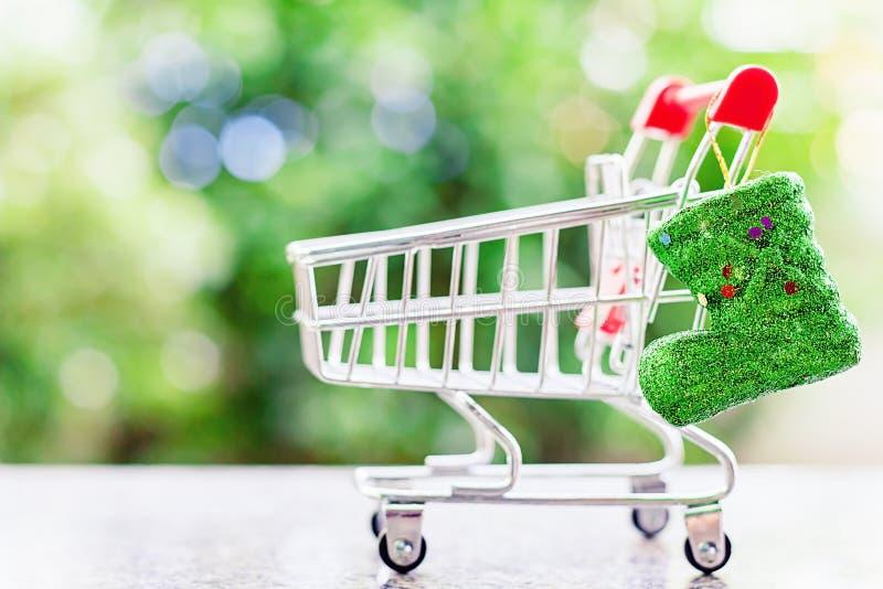 Bota del brillo de Navidad con el mini carro de la compra o carretilla contra azul fotografía de archivo