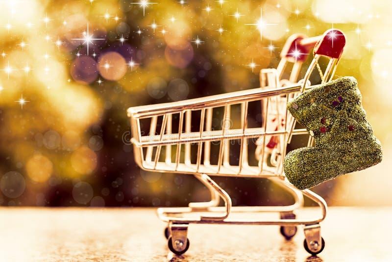 Bota do brilho do Xmas com o mini carrinho de compras ou trole contra azul foto de stock royalty free