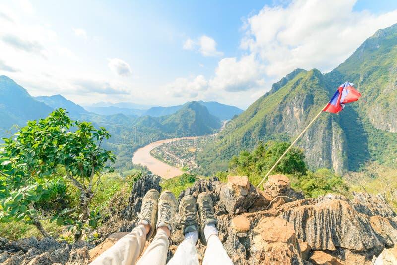 Bota trekking dos pares na parte superior da montanha na vista panor?mica de Nong Khiaw sobre o destino do curso de Laos do vale  fotos de stock