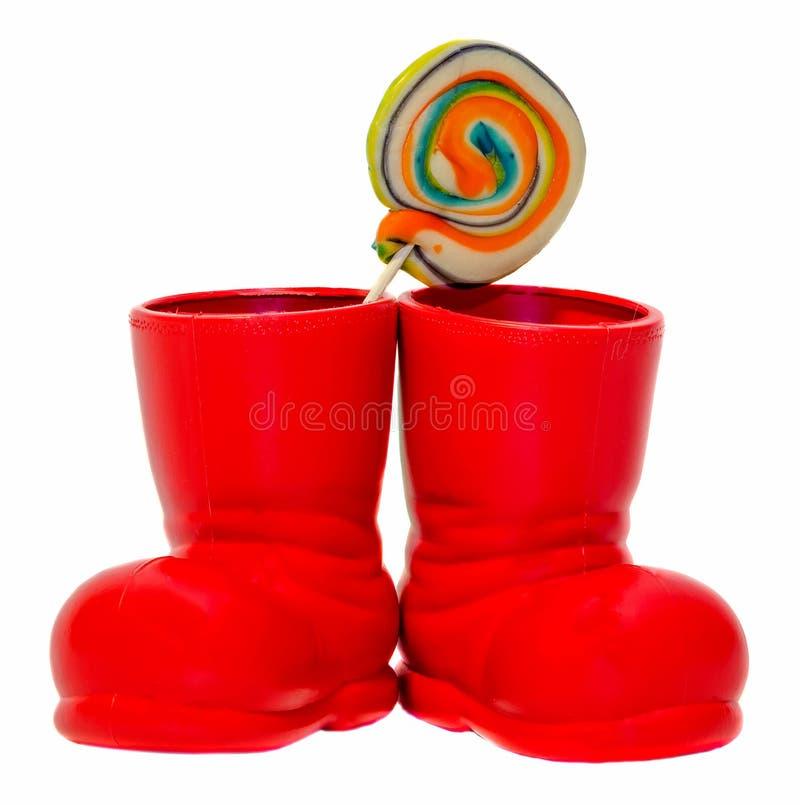 Bota vermelha de Santa Claus, sapata com os pirulitos doces coloridos, candys Bota da São Nicolau com presentes dos presentes fotos de stock royalty free