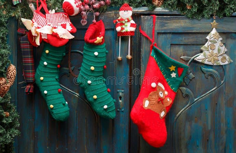 A bota vermelha do ` s de Santa, as meias verdes, o ramo sempre-verde com cones do pinho e o Natal brincam em portas azuis do ves imagens de stock