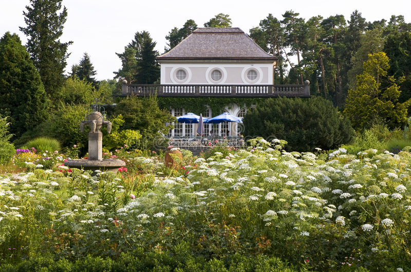 Botanic garden-munich. Café with terrace and blue sunshades in the botanic garden of munich. The café is surrounded by an romantic arrangement of green stock photo