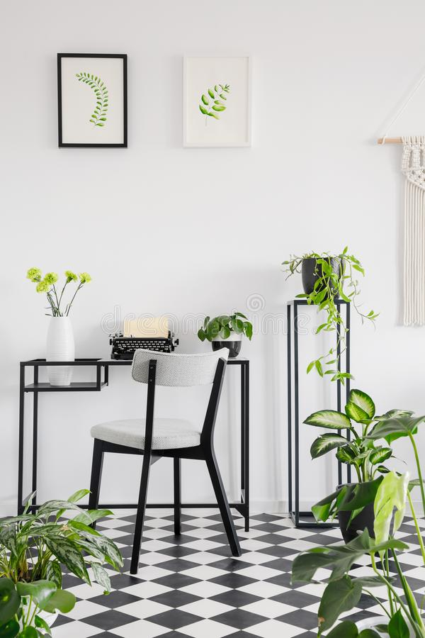 Botanical home office interior with a desk, chair and graphics on the wall. Real photo stock images