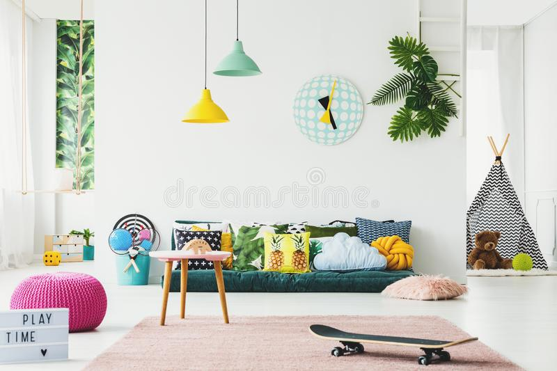 Botanical kid`s room. Interior decorated with banana leaves, green mattress, patterned cushions and tent on the side royalty free stock photo